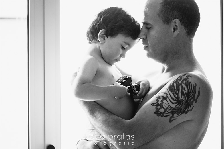 Filho ao colo do pai com tatuagem