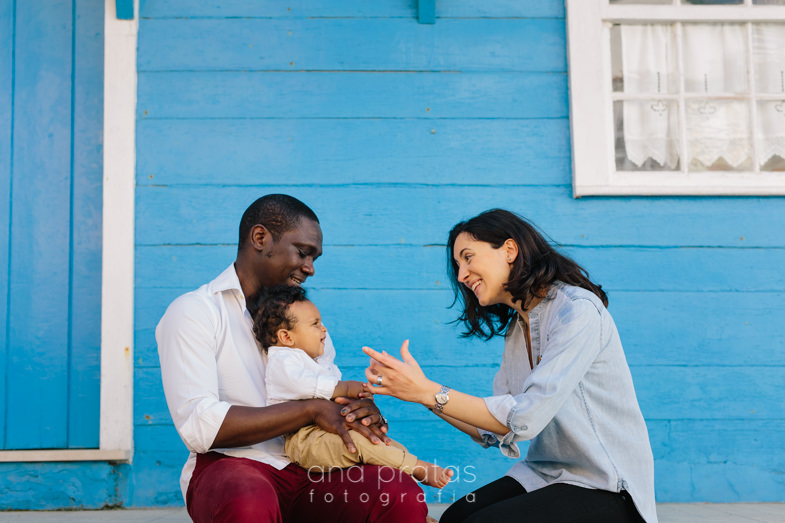 mom and dad playing with their son in front of a blue house