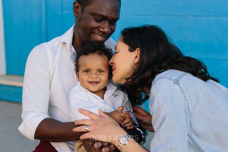 ao colo do pai enquanto mãe dá um beijo na criança
