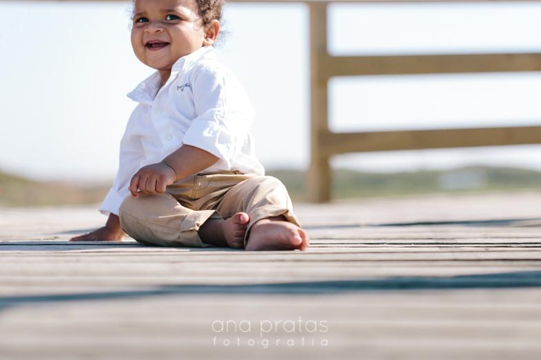 bebé com olhar divertido sentado nos passadiços da praia