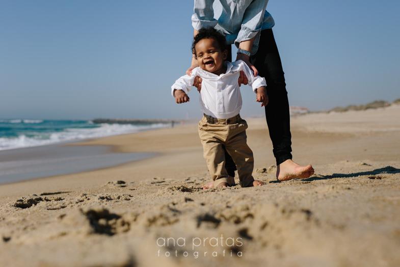 mãe segura bebé enquanto tenta caminhar na praia