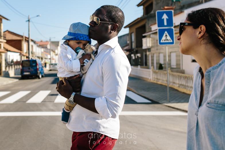 bebé cansado ao colo do pai sob o olhar ternurento da mãe nas ruas da costa nova