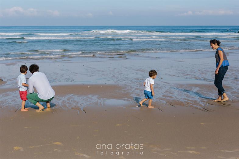 família a brincar à beira-mar