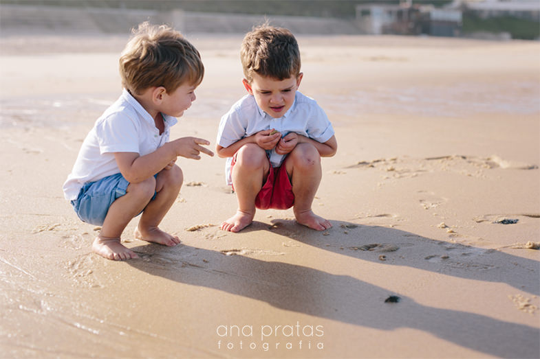 little brothers having a chat by the water at the beach