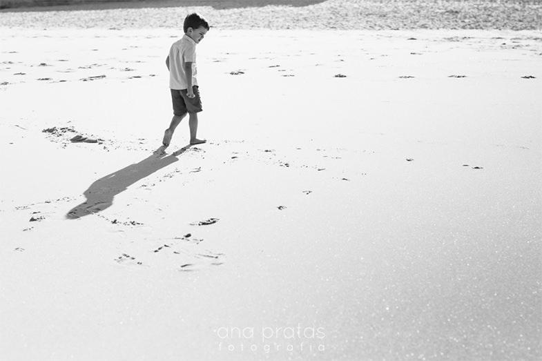 criança a caminhar na praia