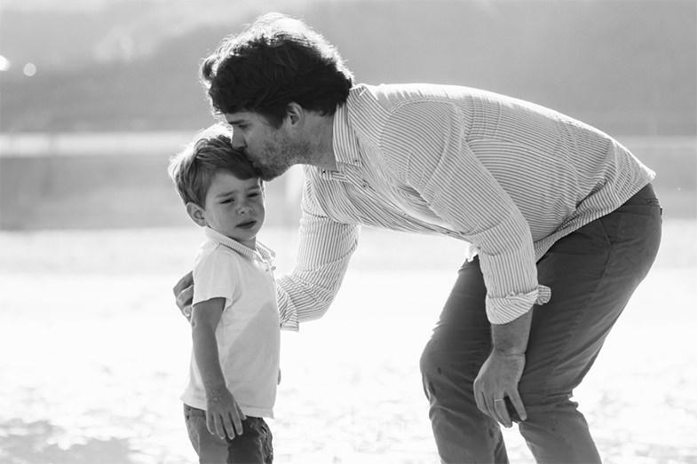 criança a chorar e pai a consolá-la com um beijo