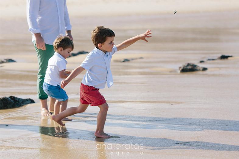 miúdo a atirar uma pedra na praia
