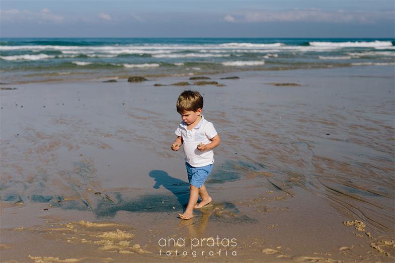 miúdo a caminhar à beira-mar com pedras na mão