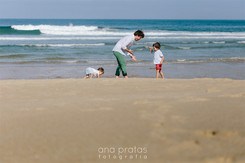 dad playing with his kids at the beach
