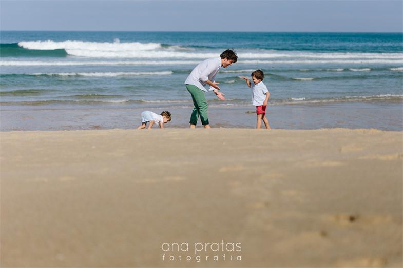 pai a brincar com filhos à beira-mar na praia