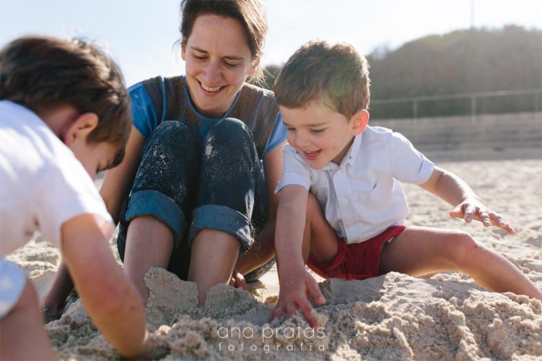 mãe a brincar com os filhos na areia