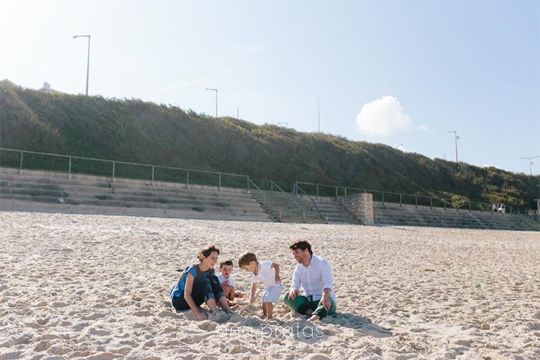 família a brincar na areia na praia