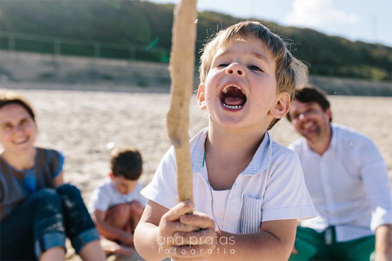 criança a brincar com um pau na praia