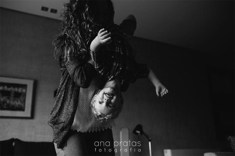 mãe a brincar com o filho virando-o de pernas para o ar
