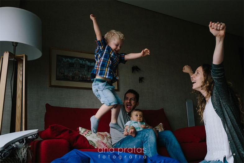 criança salta do sofá enquanto toda a família entra na brincadeira