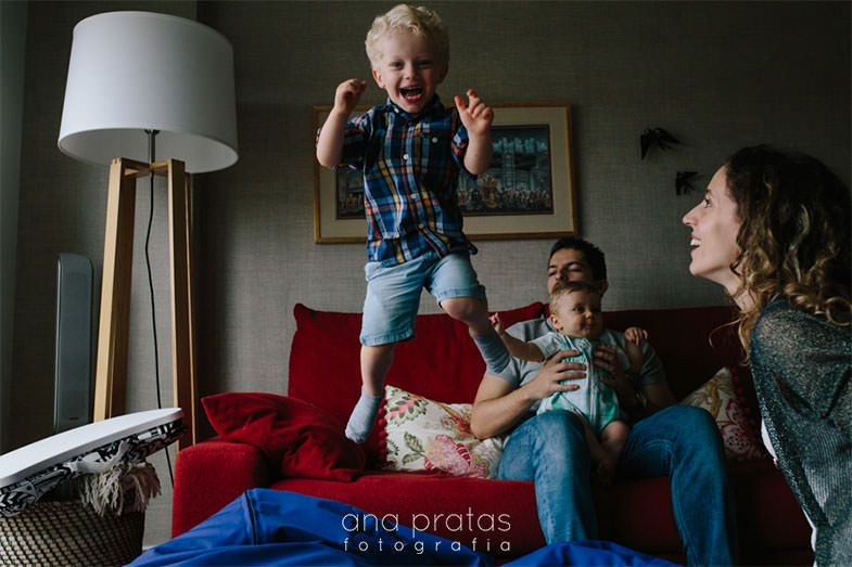 kid laughing wilhe jumping out of the sofa with his family engaged with him