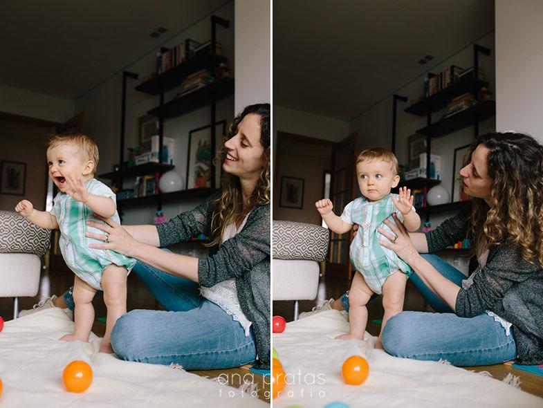 bebé divertido de pé apoiado pela mãe