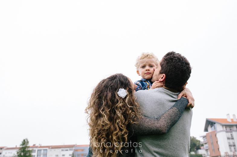 Pais de costas com o filho ao colo que olha para a câmara