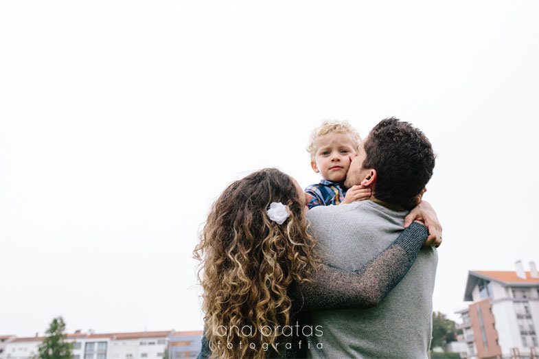 parents hold their son who looks over their back