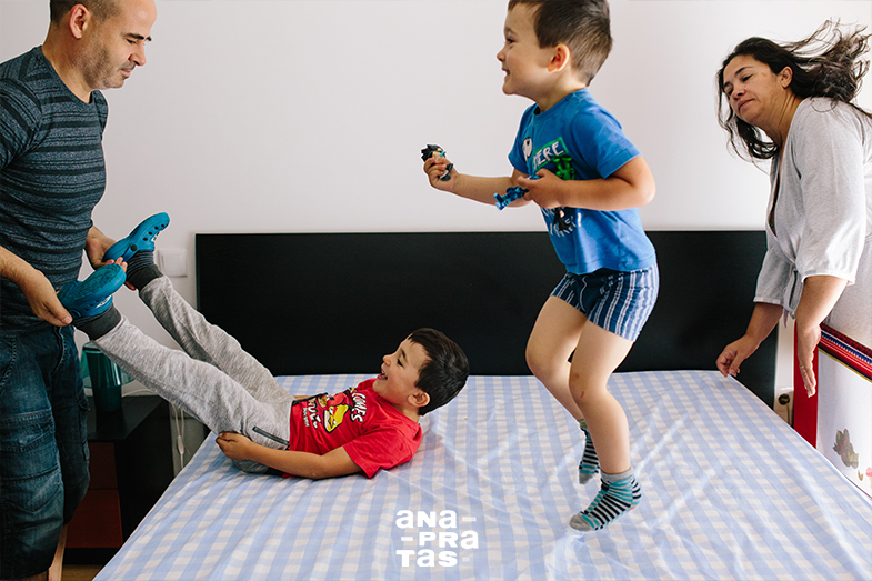 kids jumpping on bed while mom tries to make the bed