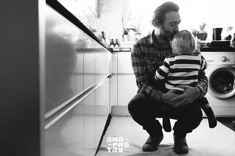 pai a abracar filho na cozinha antes de sair para o trabalho