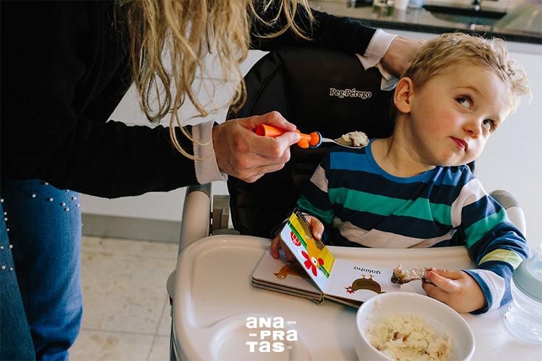Mãe a tentar dar comida a criança