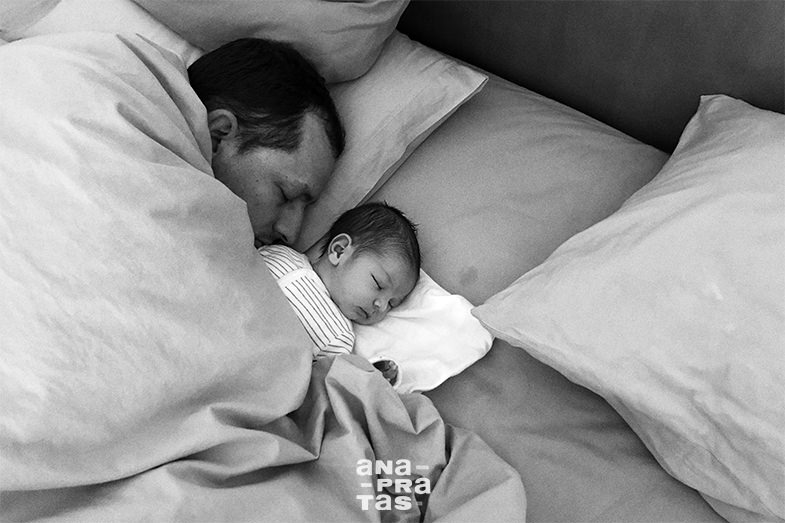 Pai e bebe a dormir na cama