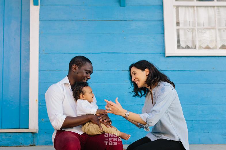 familia com criança pequena à frente de uma casa azul