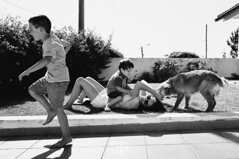 Familia e cão a brincar no jardim