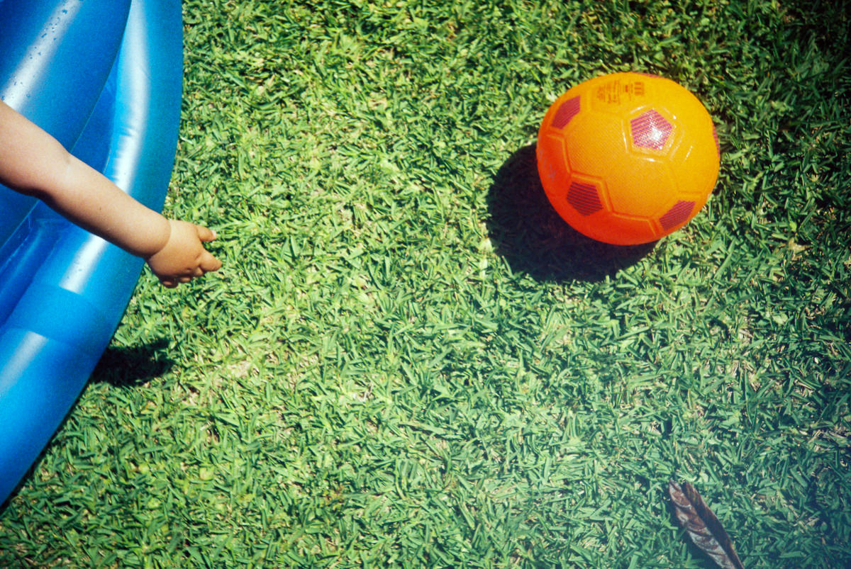 Detail of a kid stretching his arm trying to reach a ball on the grass.