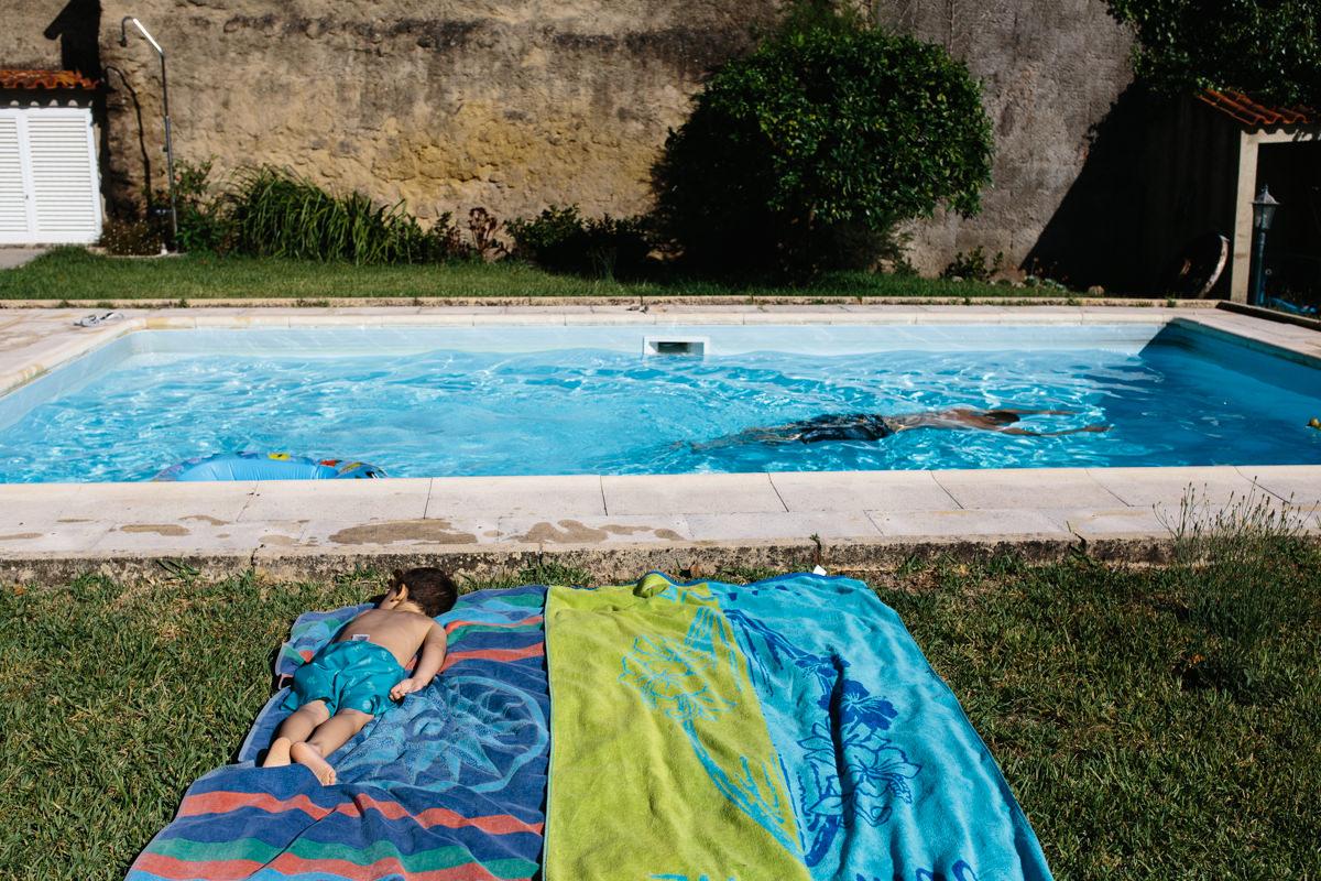 crianca deitada na toalha à beira da piscina