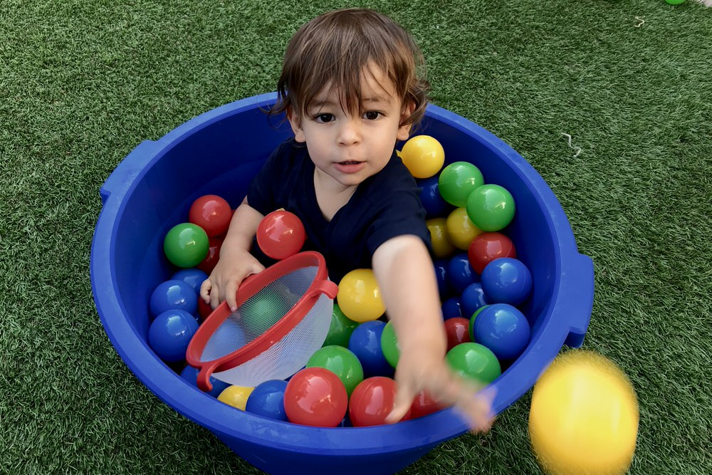 Criança dentro de bacia a brincar com bolas de plástico
