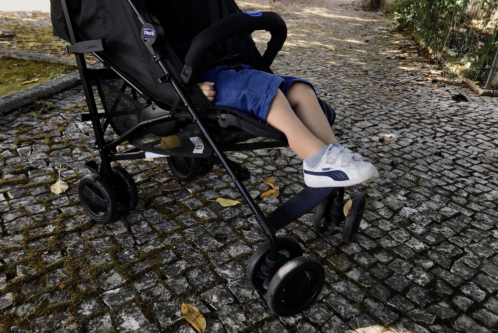 Kids feet coming out of stroller while he takes a nap