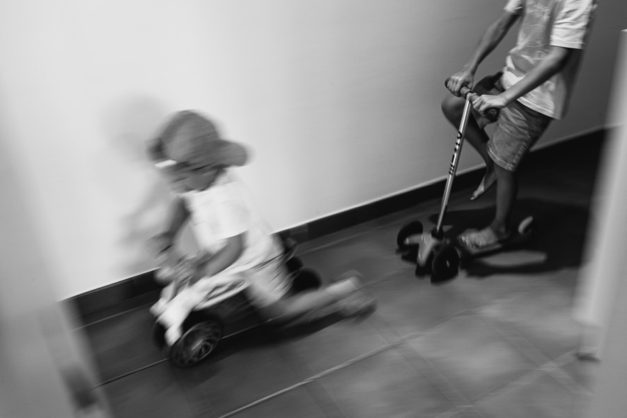 children racing on scooters at home