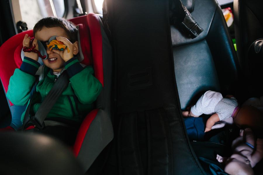 criança dentro do carro com brinquedos