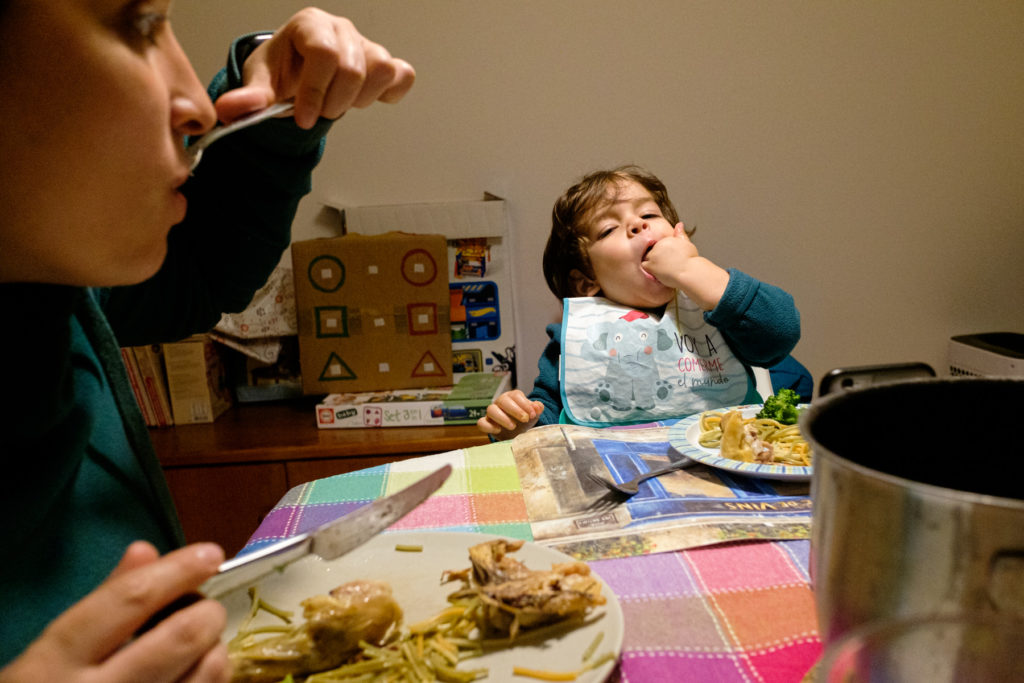 meal at the table, child eating with hand in mouth, mother eating