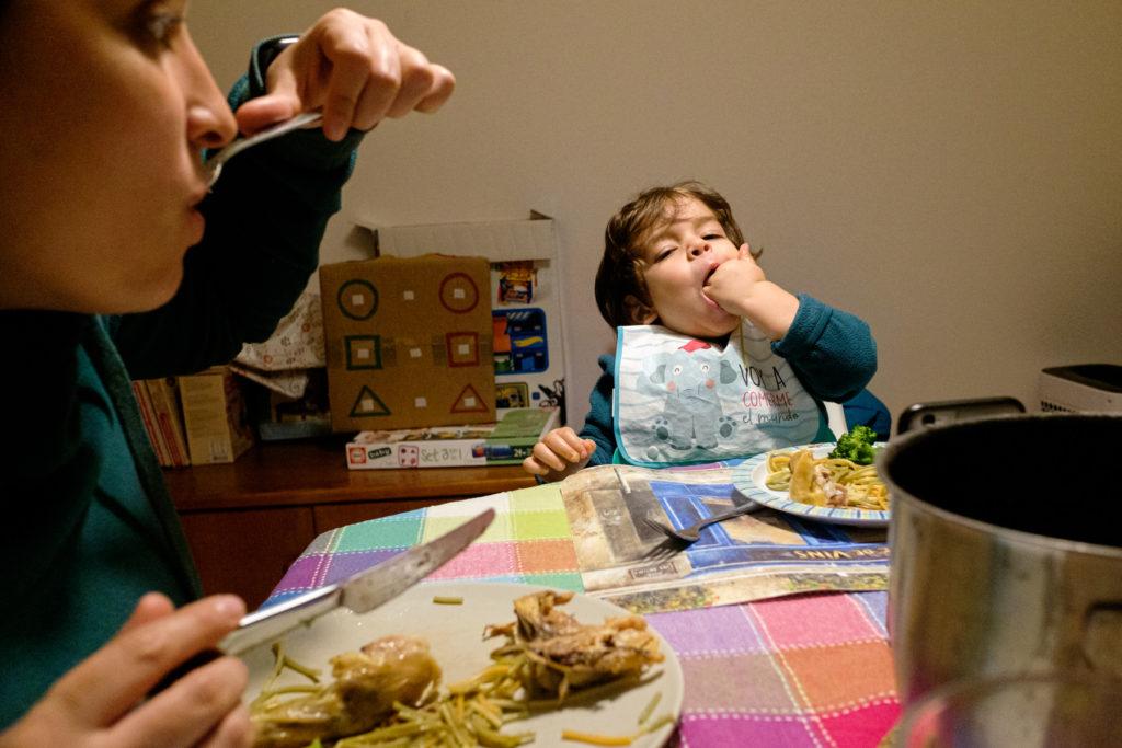 refeição à mesa, criança a comer com a mão na boca, mãe a comer