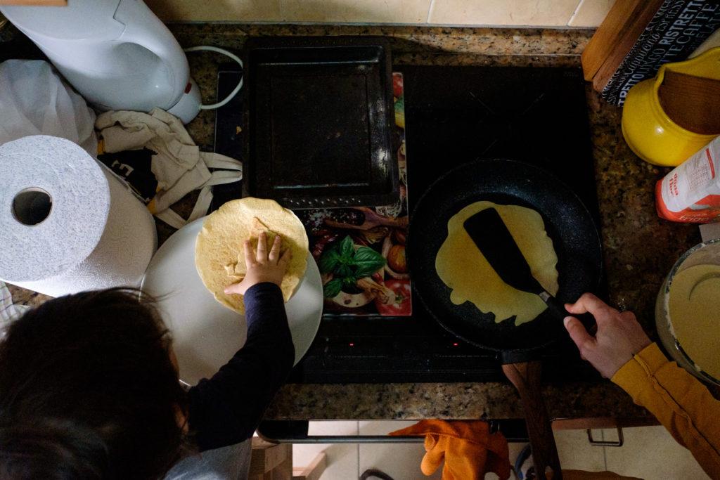 fotografia tirada de cima com uma criança e um adulto a fazerem crepes