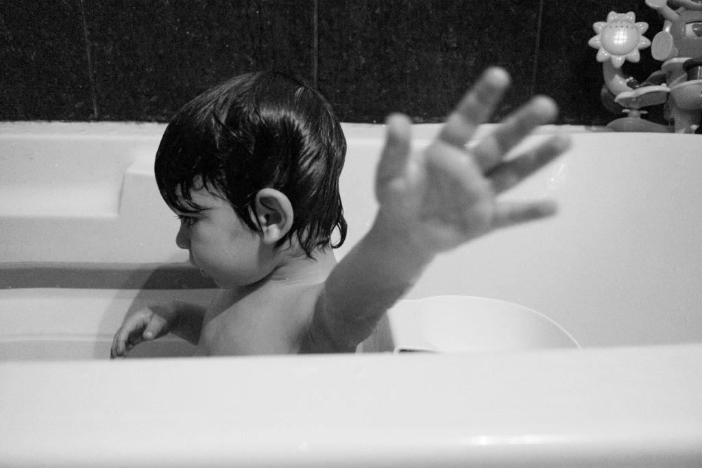 criança no banho, mão esticada