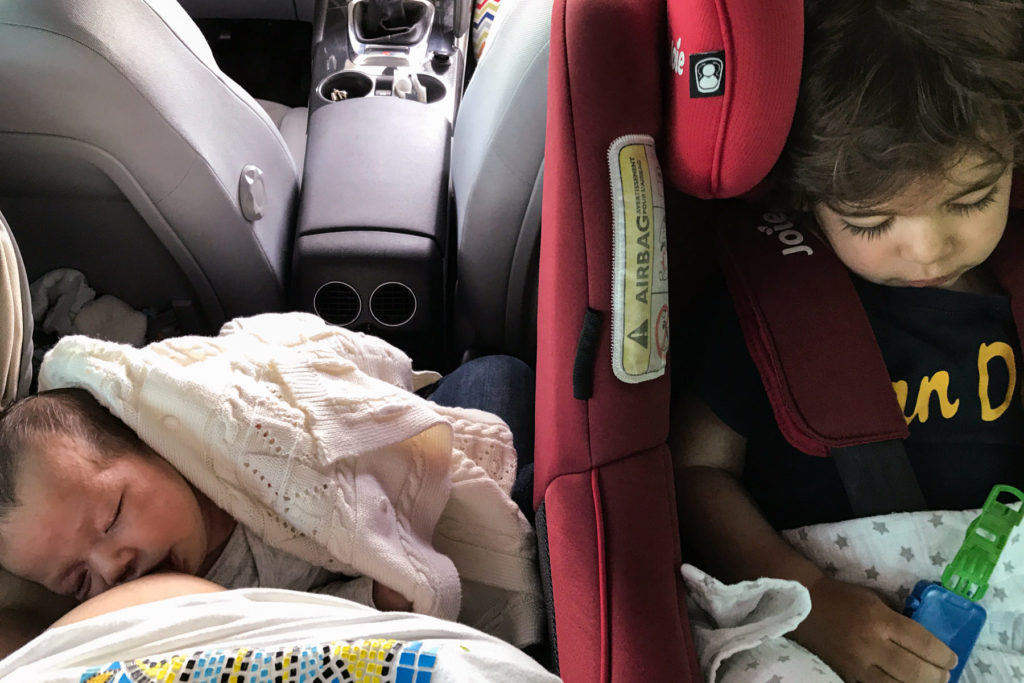 photo inside the car, baby being breastfed and child in the car seat
